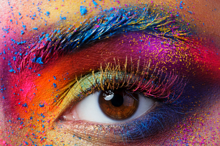 Foto de Close up view of female eye with bright multicolored fashion makeup. Holi indian color festival inspired. Studio macro shot - Imagen libre de derechos