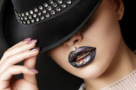 Photo for Young woman with fashion make up hiding her eyes under black hat. Fashion beauty portrait. Modern makeup. Dark lips with colorful metallic tints. Studio shot - Royalty Free Image