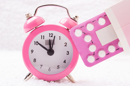 Photo for medicine and birth control. alarm clock and contraceptive pills - Royalty Free Image