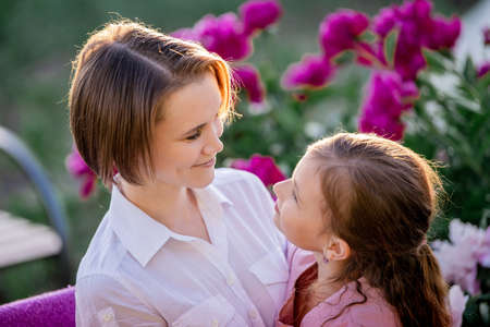 Photo pour Happy family relationships. Mom and daughter sit on a bench and chat in the garden among the flowers on a sunny summer evening. - image libre de droit