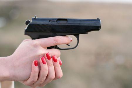 woman's hand holding a gun