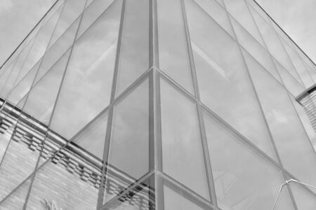 Photo pour Curtain wall made of toned glass and steel constructions under sky. A fragment of a building. Black and white. - image libre de droit