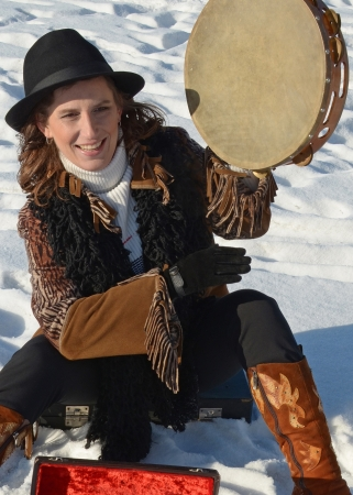 Nice girl in a hat with a tambourine in the winter on the city waterfront  Irkutsk