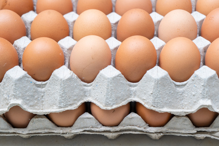 Foto de Chicken eggs in paper carton box, fresh raw eggs - Imagen libre de derechos