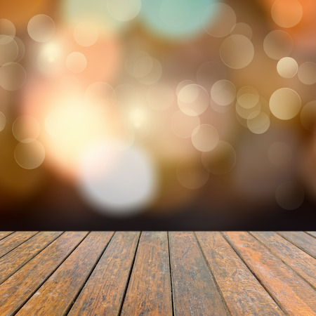Foto de Old wooden deck table with a sparkling bokeh of party lights in the black background - Imagen libre de derechos