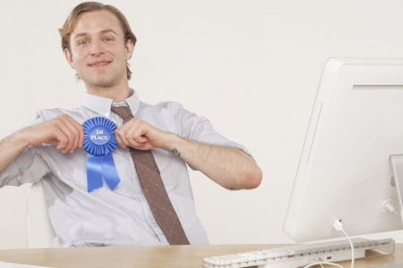 professional man sitting at desk with award ribbon