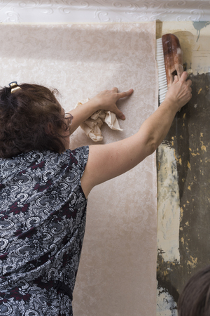 Women glue the wallpaper on the wall in the room