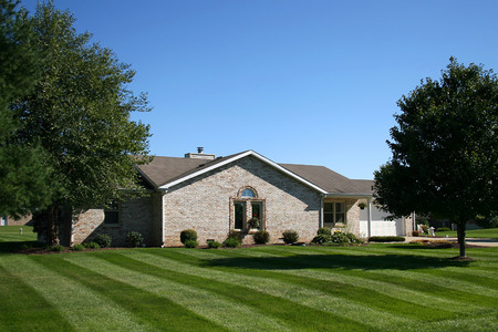 light brick suburban home with manicured lawn
