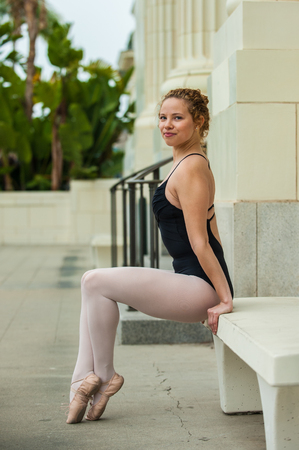 Beautiful and young ballerina seated with toes pointed.