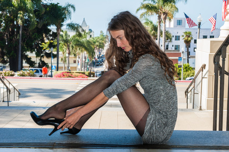 Pretty backlit brunette in black pantyhose, short dress, and pumps seated over Downtown adjusting her shoe.の写真素材
