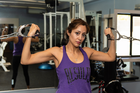 Young Latina fitness trainer holding double bicep pose using cable crossover machine in gym.