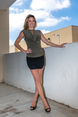 Young and attractive woman showing confident stance in black heels while wearing tan pantyhose.