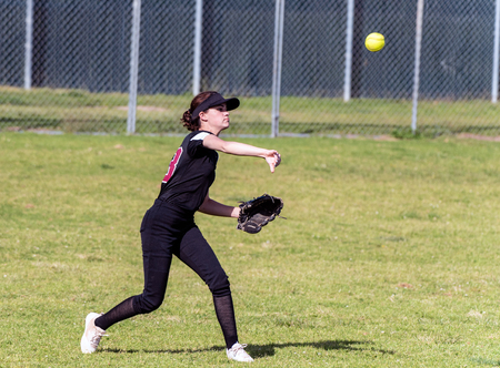 Foto de Skilled teenage softball player releasing a quick throw after making a defensive catch in the outfield. - Imagen libre de derechos