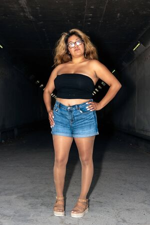 Photo pour Latina female dressed in shiny, suntan pantyhose, open toe sandals, while standing in confident pose with hands on hips in dark tunnel. - image libre de droit