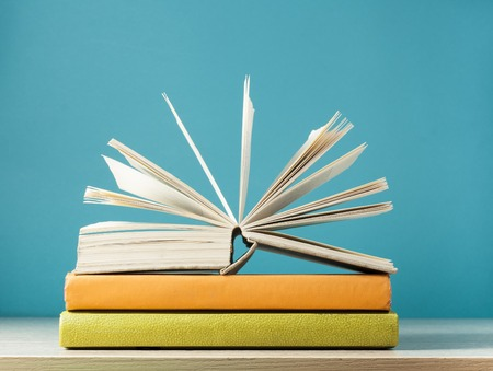 Composition with open book, hardback books on wooden table and blue background. Back to school. Education background.