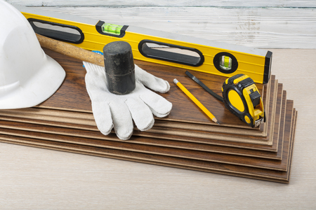 Carpentry concept.Different tools and white safety helmet, gloves on the new laminate flooring.Copy space for text.
