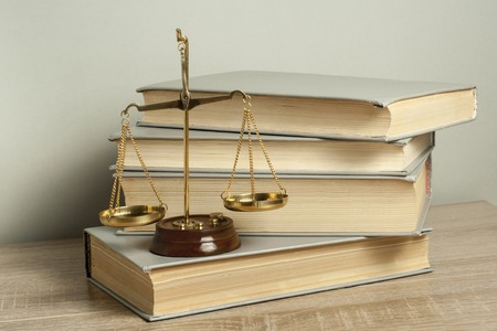 Law concept. Scales of justice with law books on table in a courtroom or enforcement office.
