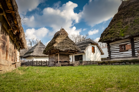 Photo pour Rustic wooden houses with thatched roofs in a village of rural eastern europe against the blue sky and some clouds in Bucharest, Romania - image libre de droit