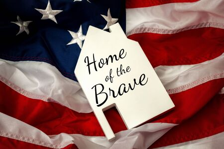 Photo pour Independence day, land of the free and home of the brave or 4th of July concept theme with a slate in the shape of a house with text and the USA flag - image libre de droit