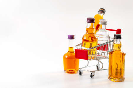 Photo pour Buy booze, shopping the liqueur aisle and purchase of alcoholic beverages concept theme with mini bottles of alcohol in a small supermarket cart isolated on white background with copy space - image libre de droit