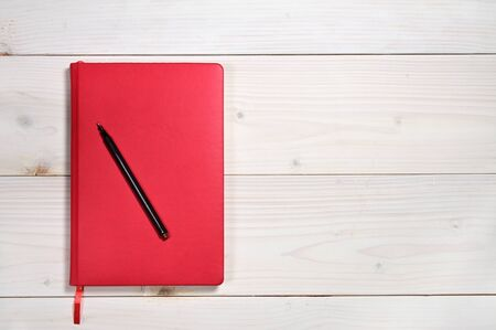 Photo for Red notebook for everyday notes on a white wooden background - Royalty Free Image
