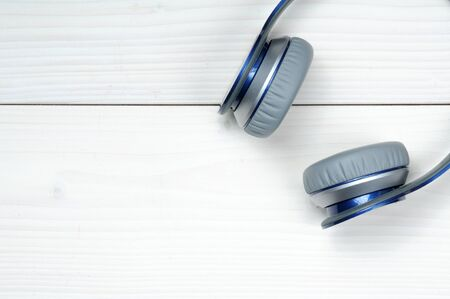 Photo pour Blue and silver modern headphones for listening to music on a white wooden background - image libre de droit