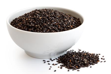 Black sesame seeds in white ceramic bowl isolated on white. Spilled seeds.