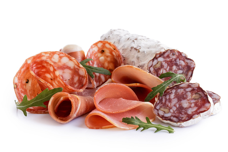 Mixed air cured sliced meats isolated on white. Rocket garnish.の写真素材