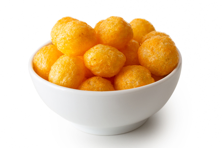 Extruded puffed cheese balls in white ceramic dish isolated on white.
