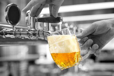 Foto de A man pouring draft lager beer into a dimpled glass mug  in a modern pub. Black and white background. - Imagen libre de derechos