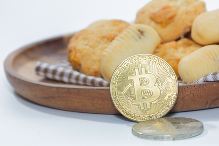 bitcoin and pile of cookies on wooden plate