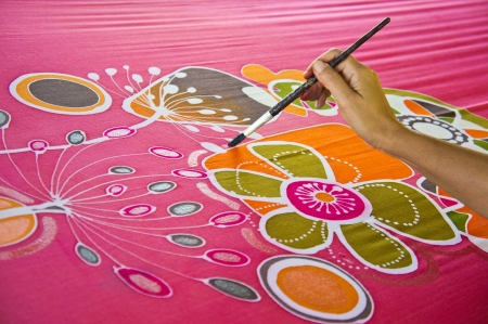 An artist carefully paint the floral/flower motif on a red silk batik fabric