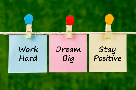 Word quotes of Work Hard, Dream Big, Stay Positive on sticky color papers hanging on rope against blurred green background.