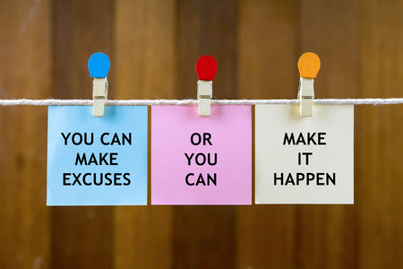 Word quotes of YOU CAN MAKE EXCUSES OR YOU CAN MAKE IT HAPPEN on colorful sticky papers hanging by a rope against blurred wooden background.