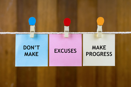 Word quotes of DON'T MAKE EXCUSES, MAKE PROGRESS on colorful sticky papers hanging by a rope against blurred wooden background.