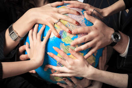 Several different people hold the globe in their hands