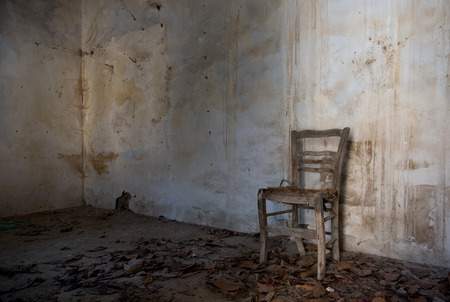 Photo pour Interior of an abandoned spooky empty room with white dirty wall and a wooden chair. Concept of abandonees and desolation - image libre de droit