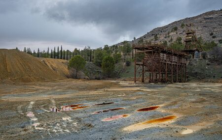 Photo for Abandoned copper mine with red toxic water and dramatic stormy cloudy sky at Mitsero area in Cyprus - Royalty Free Image