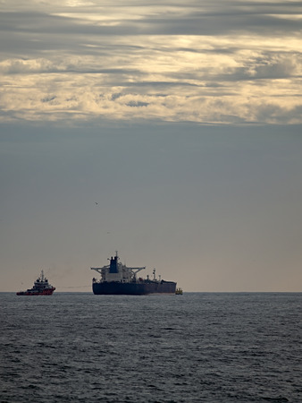 Tanker being helped by tugboat during discharge maneuvers off the coast in the evening