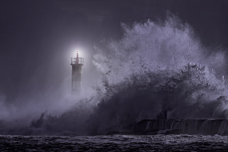 Photo pour River mouth lighthouse seeing big stormy sea wave at night - image libre de droit