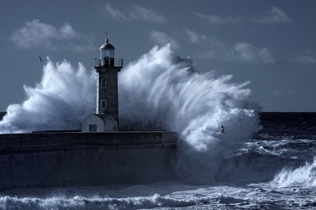 Photo pour Stormy waves over old lighthouse and pier of the Douro river  mouth entry. Used infrared filter. Toned blue. - image libre de droit