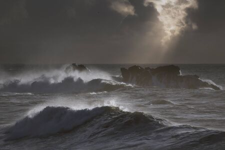 Photo pour Dark stormy seascape with light rays trough clouds at sunset - image libre de droit