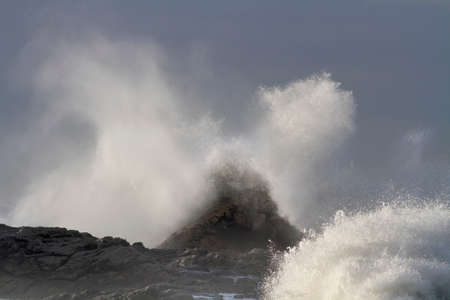 Photo pour Storm on the coast seeig big wave breaking over rocks and cliffs seeing splash and spray - image libre de droit