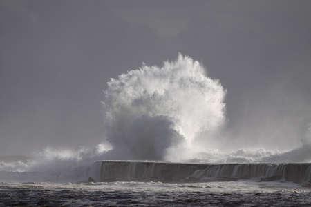Photo pour Stormy wave splash. Ave river mouth pier and beacon, Vila do Conde, north of Portugal. - image libre de droit