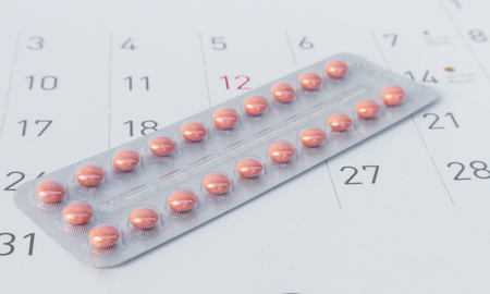 Close up birth-control pill with date of calendar background, health care and medicine concept
