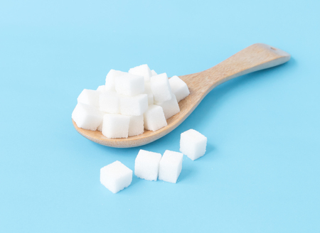 Closeup sugar cubes on wooden spoon white blue background