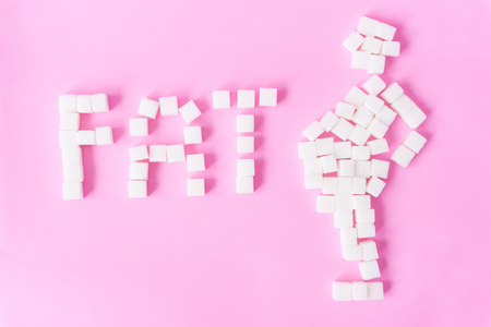 FAT text and fat man shape with sugar cubes on sweet pink background, food and healthy concept