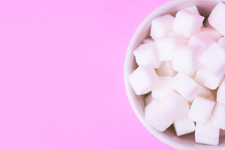 Closeup sugar cubes on bowl with pink background, health care concept
