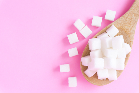 Closeup sugar cubes on wooden spoon with pink background, health care concept