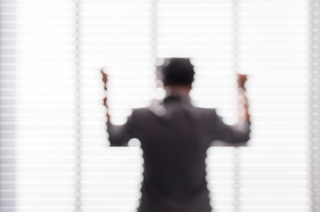 Blurred business man feel happy with his goal achievement, stands near the window in office building.